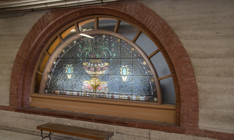 A stained glass window under a building walkway.