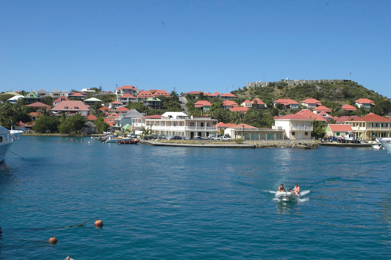 A view of La Presqu'ile, a hotel on the Gustavia harbor. It is the white, two-story building with the veranda on the two visible sides.