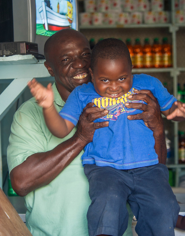 Father holds his grandson for a quick photo in a bar, Basseterre, St Kitts