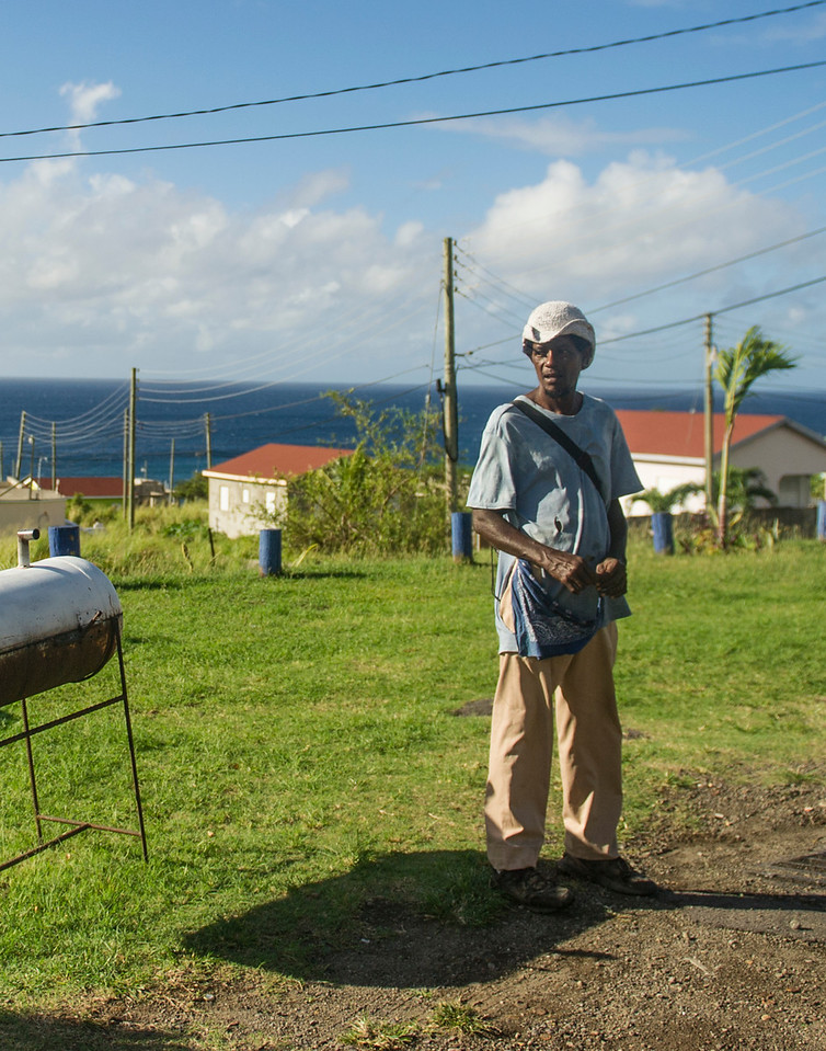 man waits patiently for a van on the southern side of the island, about 5 miles from Basseterre, St Kitts