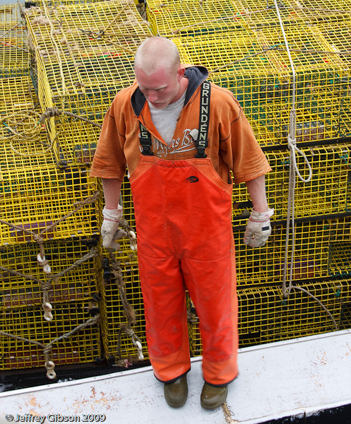 IMAGE 11:  Here is a lobsterman with his traps.  I learned that the flourescent outfits are for a reason. This is a dangerous profession.  One of the hazards with this profession is having a rope from a trap wrap around a lobsterman's leg as he is releasing them into the water.  The trap will pull them over.  The orange outfit helps the rescuers spot the body.