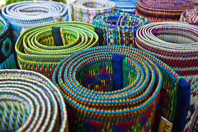 Colorful mats for sale by a street vendor