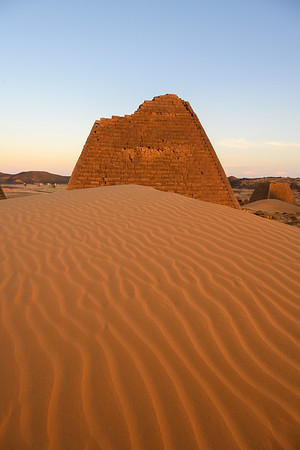 Sunset over sand dunes and pyramids at the royal Kushite necropolis of Meroë.  This cemetery, used between 350BC to 300AD, contains over fifty pyramids and served as the necropolis for the capital city. The pyramids are a UNESCO World Heritage site.  The Kingdom of Kush flourished in modern day Nubia between 2000 BC - 350 AD, successfully invading Egypt during the 25th Dynasty and establishing a line of influential kings and queens who ruled along the Nile.