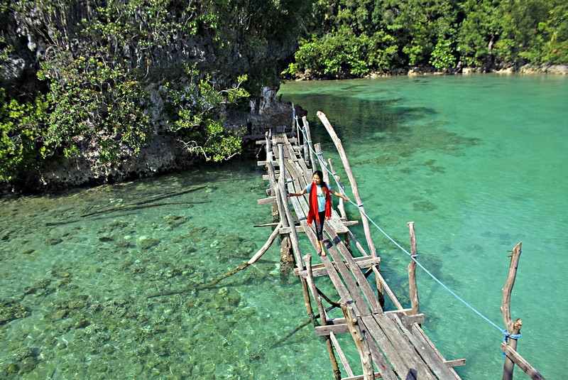 A tourist walks in the small wooden bridge linking the building to one of the lagoon's rock formations.  (Erwin M. Mascarinas)