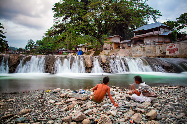 Local fishermen relax next to a waterfall in 'downtown' Bukit Lawang. Occasionally wild orangutans will venture into town to play and feed amongst the trees in the background.