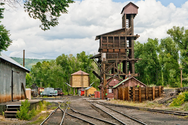 The first wooden tower is an elevator that hauls coal up to a level where it can be dropped into the locomotive's tender. The tender, (the little car behind the cab) also holds water. The water tower is behind the coal tower.
