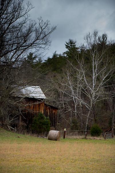Barn and haybail with overcast sky