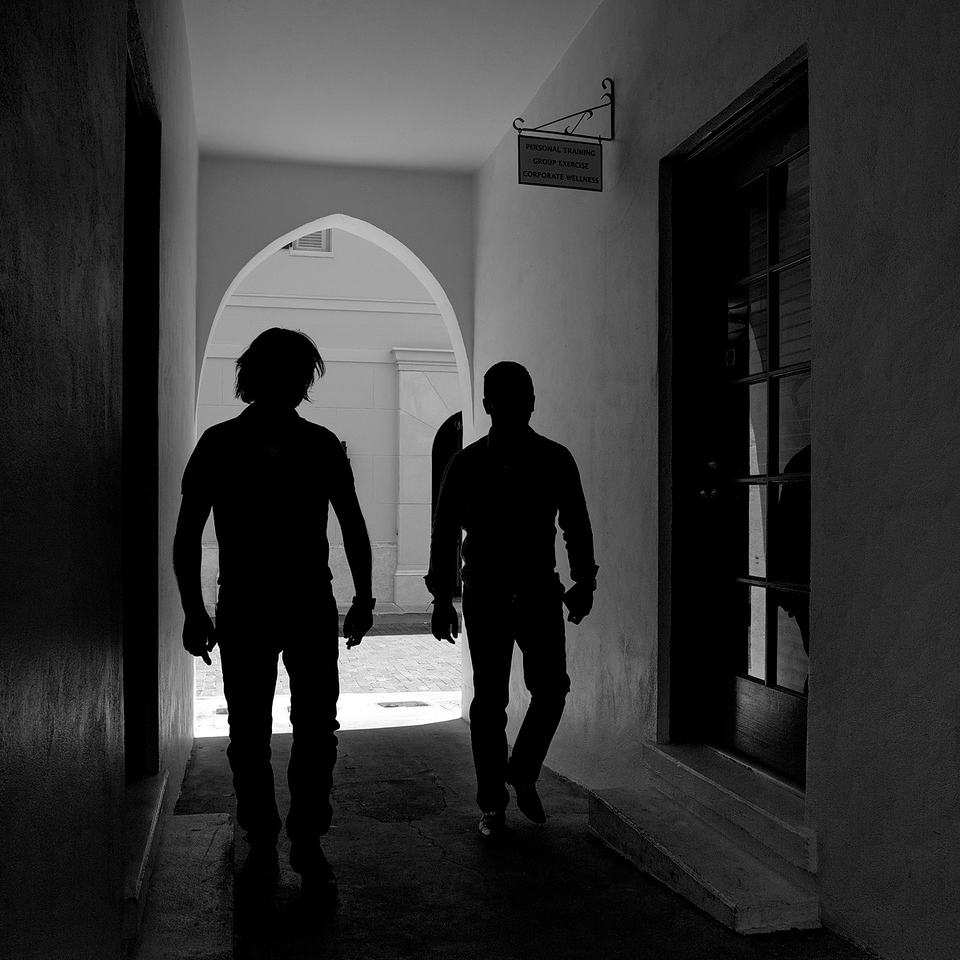 Two young fellows walking through the hallway. It was so dark in there, and the walls virtually colorless that there was no point in retaining the little color that was in this photo. Besides, I think it looks better  with black and white silhouettes anyway.