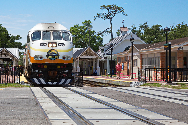 """Here i s another view of the SunRail engine. It has three cars behind it. It is stopped to load and unload passengers. It is not really in the crossing, but the gates are down, infuriating car drivers who must wait even though the crossing has no train in it. This is a commuter train. It has a few poles at the ends of the cars for standing passengers to hang on to, but it has no """"straps."""" They want people to ride it to relieve traffic on the roads, but I guess they don't want too many people to ride it, otherwise they'd have straps. Which means it will never make money and I and other tax payers will subsidize it forever, because once established, a bureaucratic entity will never die. The sun will never set on SunRail."""