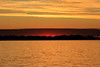 Cropped image looking down the Bay of Quinte. Purple clouds along the horizon, yellow skies and water.
