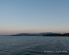 With the cruise underway, the moon can be seen up in the sky as sunset approaches