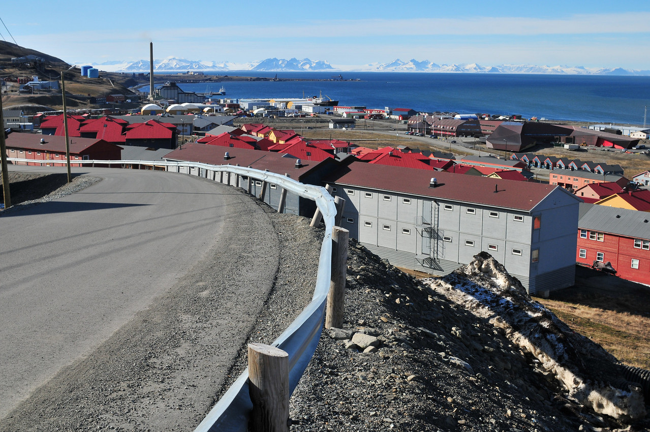 Looking west from the B2 (north east) part of Longyearbyen. The large structure to the right is UNIS, where the University and museum are located.<br /> <br /> All these homes are company owned, and rented - almost no one owns their own home on Svalbard, but there are a few exceptions.