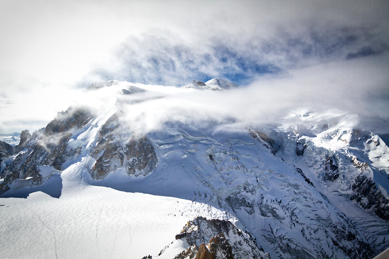 Aiguille du midi: The parting clouds allowed for a quick view of the summit of Mont Blanc.  Note the paths of footsteps on the bottom left of hikers.