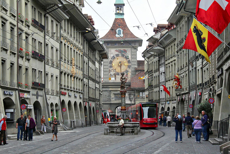 """One of downtown Bern, Switzerland's few concessions to modern times is a slick light rail system that moves carefully and quietly thru the """"pedestrian only"""" streets. In the center is the women's prison tower, and the Zyglogge Clock from the previous photo is on the other side if it."""