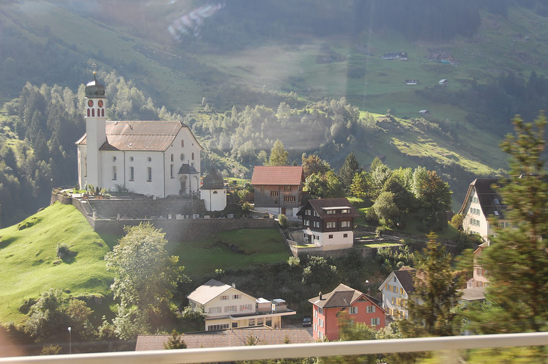 View from the William Tell Express train between Luzern and Lugano. This is the church at Wassen. You see this church three times, from different perspectives, during the journey. The train ingeniously winds in a spiral around the mountains.