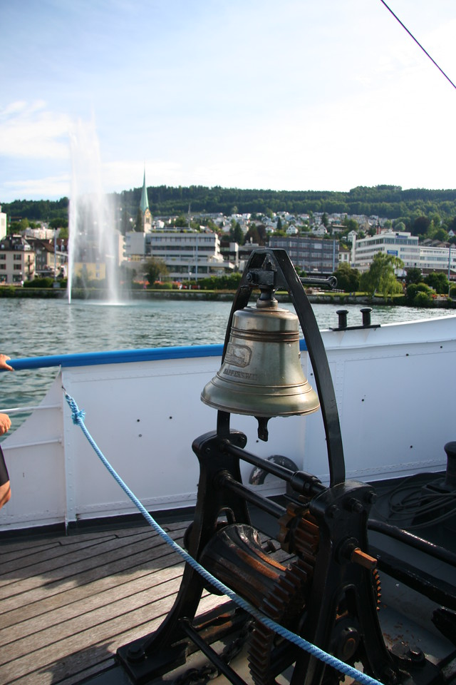 Bell at the bow of the ferry, and one of the many fountains in the lake in the background.