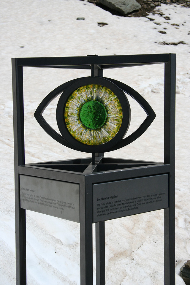 "The first glass eye is at the halfway point. It reads:<br> ""The plant world. Water and light - and the Earth becomes green. Plants grow, rooted in the earth, facing the sun. They live because they change the world and reproduce. Plants sing a silent tune in their beauty. Listen."""