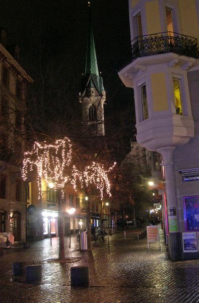 The church spire glows over the street scene in old town - Zurich - Switzerland