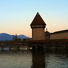 Lucerne's famous covered wooden Spreuerbridge over the river Reuss with the full moon rising over the alps.