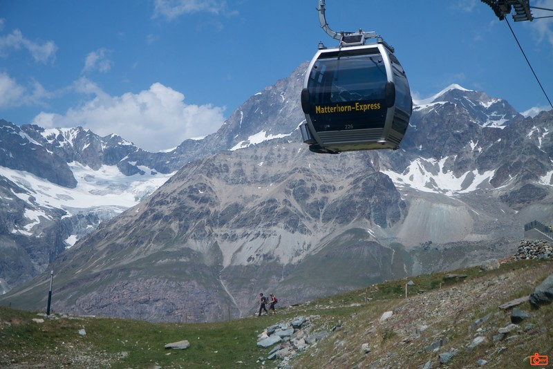 A typical view of Switzerland - a cable car ascending, hikers on a well-marked trail and the snow capped Alps in the background.<br /> IMG_9675