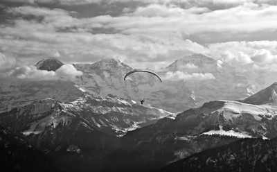 A paraglider floats towards (left to right) Eiger, Mönch and Jungfrau. Jungfraujoch is visible just above the chute. From Niederhorn.