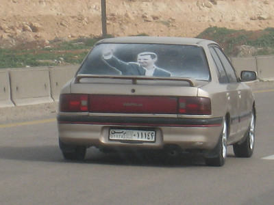 President al Assad's smiling visage in the rear window of a passing car (same thing is common in the UAE except here in Dubai its picture of the Rulers.)