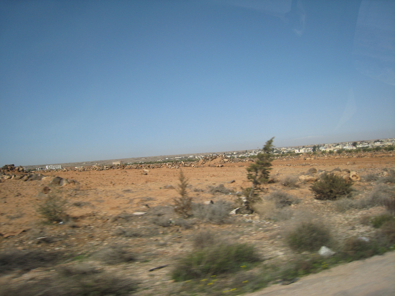 "On the road to Bosra about 100kms from Damascus.  In the distance the town of Suweida, the birthplace of singer, actor, composer and ""King of the Oud"", Farid al Atrashe."