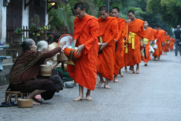 over 600 local monks walk the city streets at dawn to receive gifts of rice and other foods for their daily needs