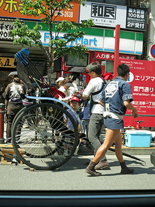 "Back on Kaminarimon. The rickshaw driver (puller?) has strong legs and good shoes. ""Rickshaw"" means ""human-powered vehicle."""