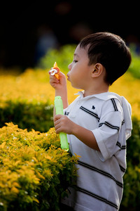 Young lad blowing bubbles...or trying