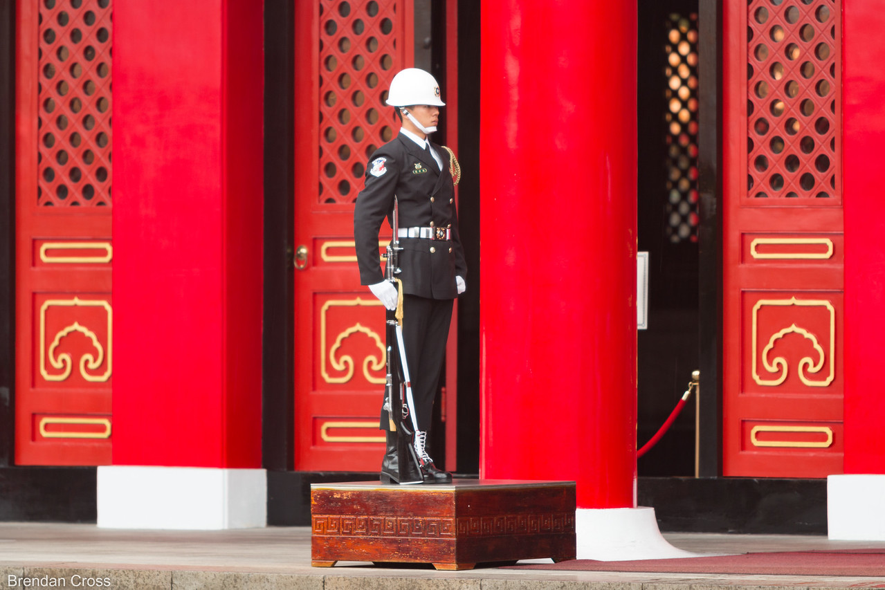 One of the two guards inside standing still at attention. At one point a Chinese tourist came up and touched his leg - I have no idea why - causing him to slam down his gun  and stomp his boot on the pedestal to show her that he didn't play. A guy working at the shrine then came over and adjusted the tassles on his upper right shoulder pad.