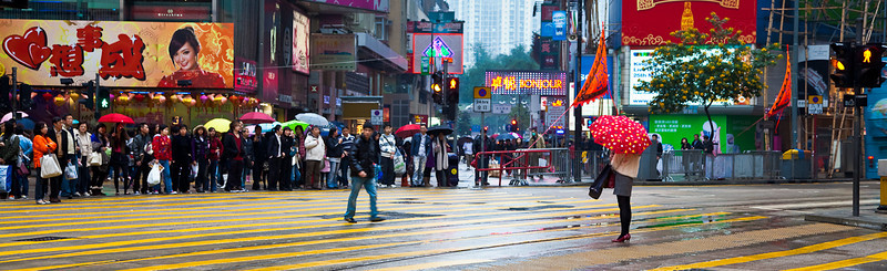Women with umbrella crossing street in Hong Kong