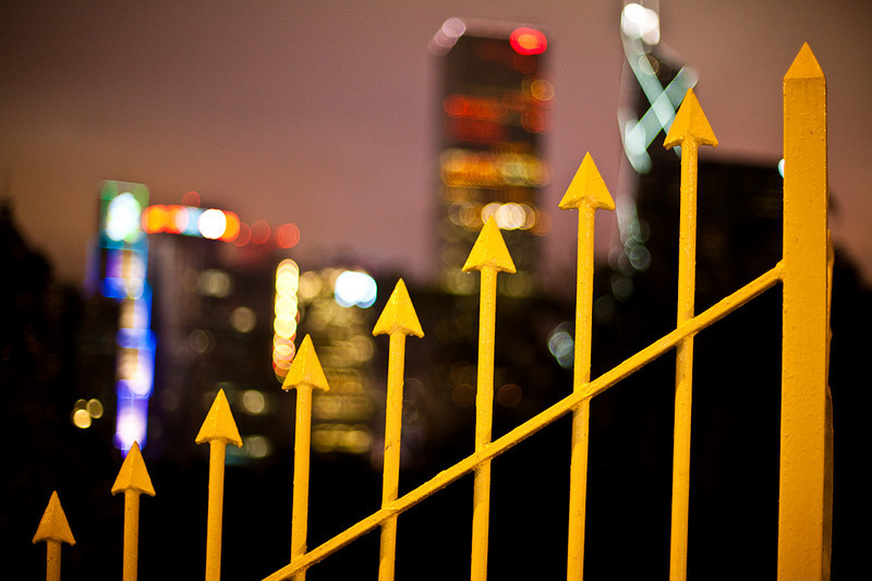 Night photo of Hong Kong and metal gate with arrows