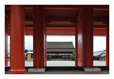 Kyoto Imperial Palace Grounds showing the Shishinden, the symbol of the Kyoto Imperial Palace,  viewed through a red gate leading into a white sand courtyard.  The Shishinden, built in the Heian style,  was completed in 1855
