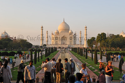Hundreds of visitors come to the Taj Mahal. The central focus of the complex is the tomb. This large, white marble structure stands on a square plinth and consists of a symmetrical building with an iwan (an arch-shaped doorway) topped by a large dome and finial. Like most Mughal tombs, the basic elements are Persian in origin. The marble dome that surmounts the tomb is the most spectacular feature. Its height of around 35 metres (115 ft). The minarets, which are each more than 40 metres (130 ft) tall, display the designer's penchant for symmetry. They were designed as working minarets — a traditional element of mosques, used by the muezzin to call the Islamic faithful to prayer. Agra, Uttar Pradesh state (UP), North India.