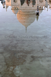 """Reflections of Taj Mahal. The garden uses raised pathways that divide each of the four quarters of the garden into 16 sunken parterres or flowerbeds. A raised marble water tank at the center of the garden, halfway between the tomb and gateway with a reflecting pool on a north-south axis, reflects the image of the mausoleum. The raised marble water tank is called al Hawd al-Kawthar, in reference to the """"Tank of Abundance"""" promised to Muhammad. Due to its shape, the dome is often called an onion dome or amrud (guava dome). The marble dome that surmounts the tomb is the most spectacular feature."""