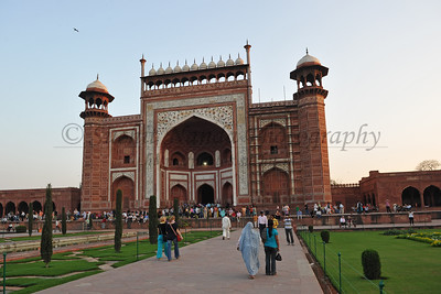 Taj Mahal. The main gateway (darwaza) is a monumental structure built primarily of marble which is reminiscent of Mughal architecture of earlier emperors. Its archways mirror the shape of tomb's archways, and its pishtaq arches incorporate the calligraphy that decorates the tomb. It utilizes bas-relief and pietra dura inlaid decorations with floral motifs. The vaulted ceilings and walls have elaborate geometric designs, like those found in the other sandstone buildings of the complex.