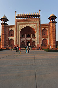 Entrance to Taj Mahal. The Great gate (Darwaza-i rauza)—gateway to the Taj Mahal. The complex is bounded on three sides by crenellated red sandstone walls, with the river-facing side left open. The main gateway (darwaza) is a monumental structure built primarily of marble which is reminiscent of Mughal architecture of earlier emperors. Its archways mirror the shape of tomb's archways, and its pishtaq arches incorporate the calligraphy that decorates the tomb. It utilizes bas-relief and pietra dura inlaid decorations with floral motifs. The vaulted ceilings and walls have elaborate geometric designs, like those found in the other sandstone buildings of the complex.Agra, Uttar Pradesh (UP), India.