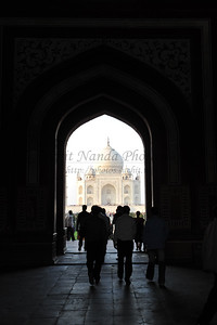 View of the main structure of the magistic Taj Mahal complex from the entrance - The Great gate (Darwaza-i rauza)—gateway. The complex is bounded on three sides by crenellated red sandstone walls, with the river-facing side left open. The central focus of the complex is the tomb. This large, white marble structure stands on a square plinth and consists of a symmetrical building with an iwan (an arch-shaped doorway) topped by a large dome and finial. Like most Mughal tombs, the basic elements are Persian in origin. Agra, Uttar Pradesh (UP), India.