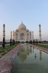 "Taj Mahal, India. A raised marble water tank at the center of the garden, halfway between the tomb and gateway with a reflecting pool on a north-south axis, reflects the image of the mausoleum. The raised marble water tank is called al Hawd al-Kawthar, in reference to the ""Tank of Abundance"" promised to Muhammad. The garden uses raised pathways that divide each of the four quarters of the garden into 16 sunken parterres or flowerbeds. Due to its shape, the dome is often called an onion dome or amrud (guava dome). The marble dome that surmounts the tomb is the most spectacular feature."