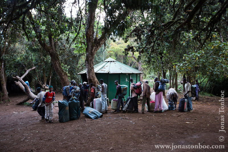 Mti Mkubwa Camp at 2750 Meters - Porters Lining Up At the Camp Office to Sign In
