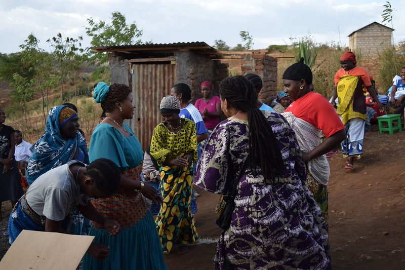 Faustina Nillan Losai and Valora K Starr share a dance of thanksgiving with women in Same after distribution of quilts, school and personal kits distribution.  photo by Shelby Morgan