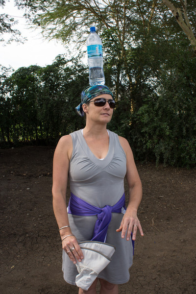 Lisa practices carrying water on her head. Note the training-sized container.