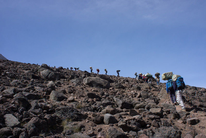 Porters pass us on the steep hike above Lava Tower.