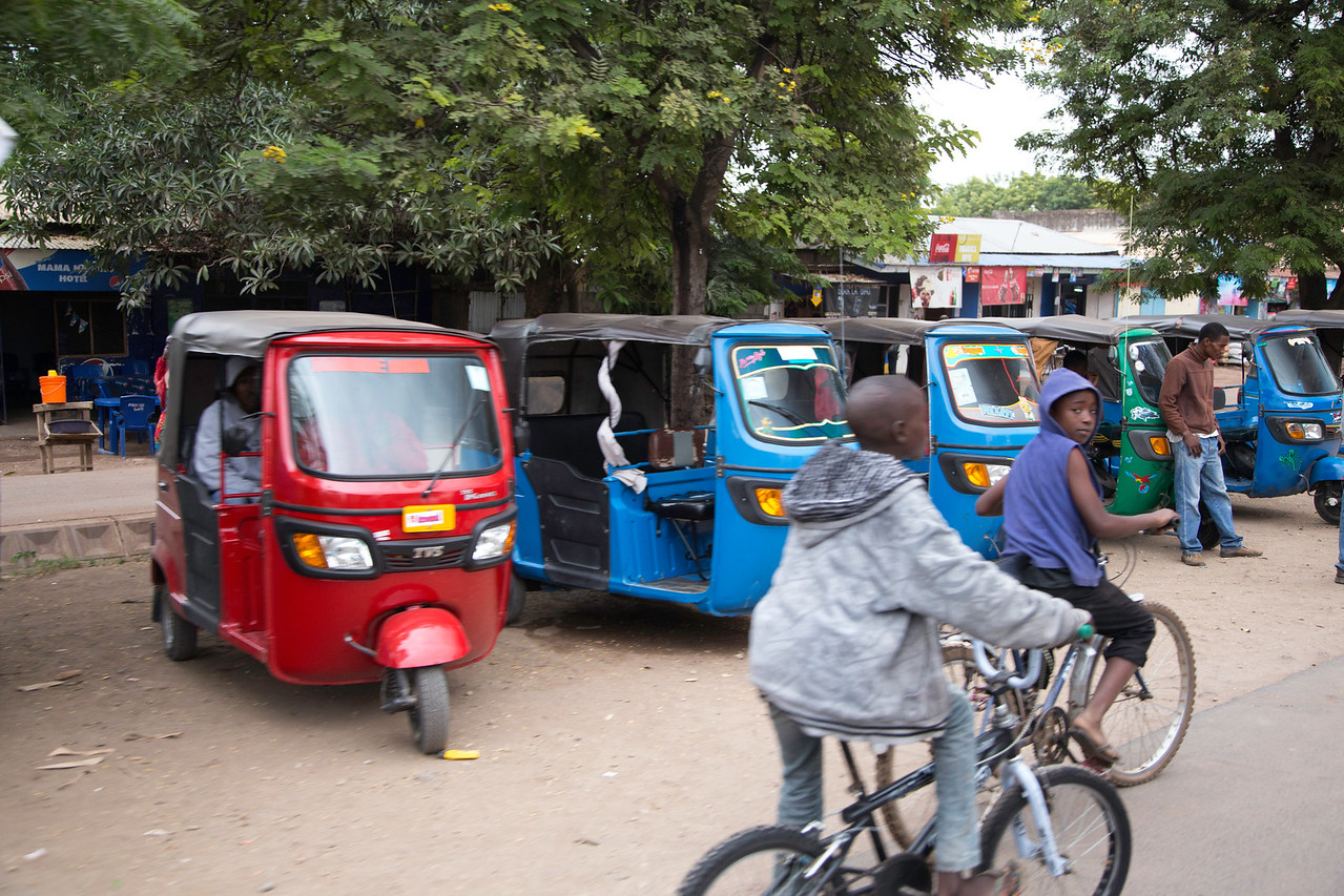 """Street scene in the small town of Karatu, a key supply stop on the northern Tanzania safari loop.  The three-wheeled vehicles are made in India and go by the local name """"tut tut"""" for the sound of their motor."""