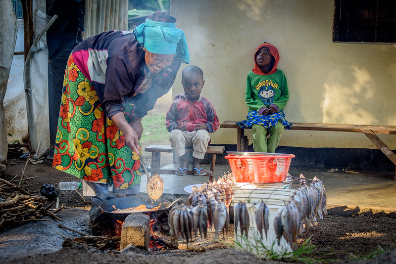 A villager fries up some fish as her children watch