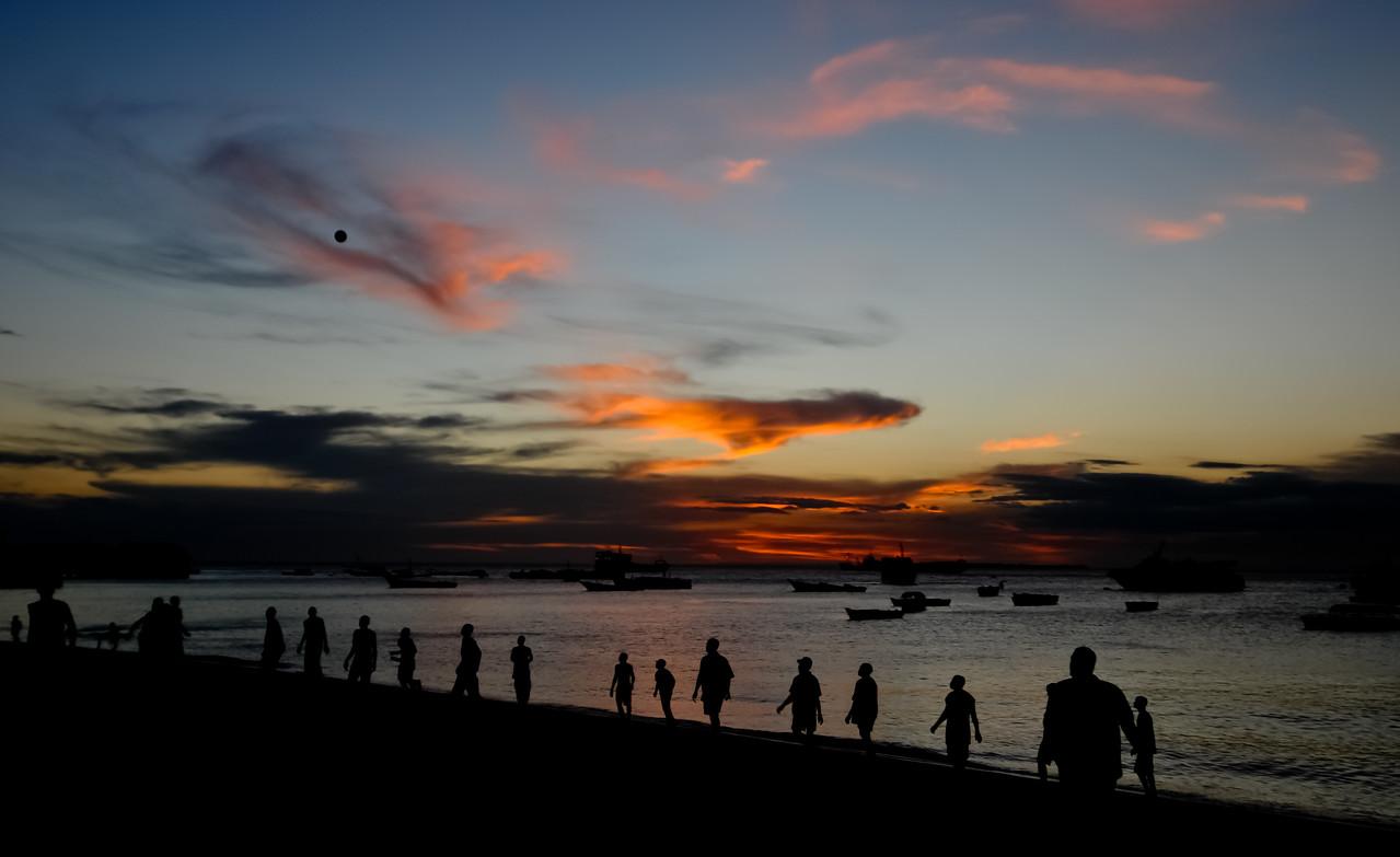 Young men playing football on the Beach at sunset, Stone Town, Zanzibar, Tanzania.