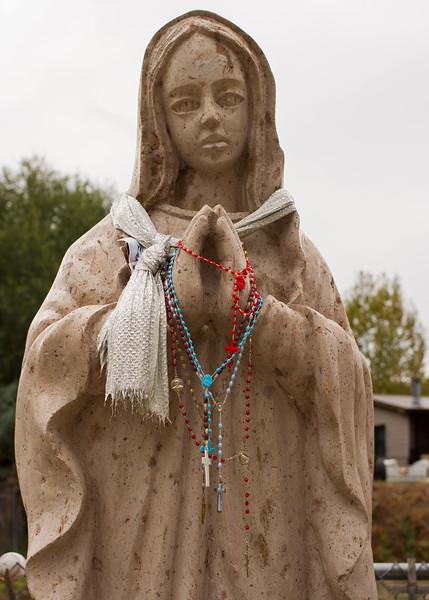 Statue with offerings. El Santuario de Chimayo, New Mexico.