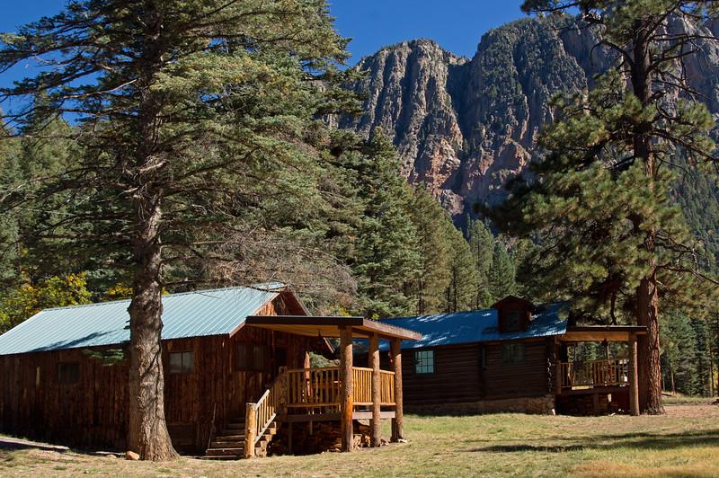 Pine Knot cabin (foreground), Corkins Lodge, Tierra Amarilla, New Mexico. The Brazos Cliffs rise 2500 ft above the Rio Brazos.