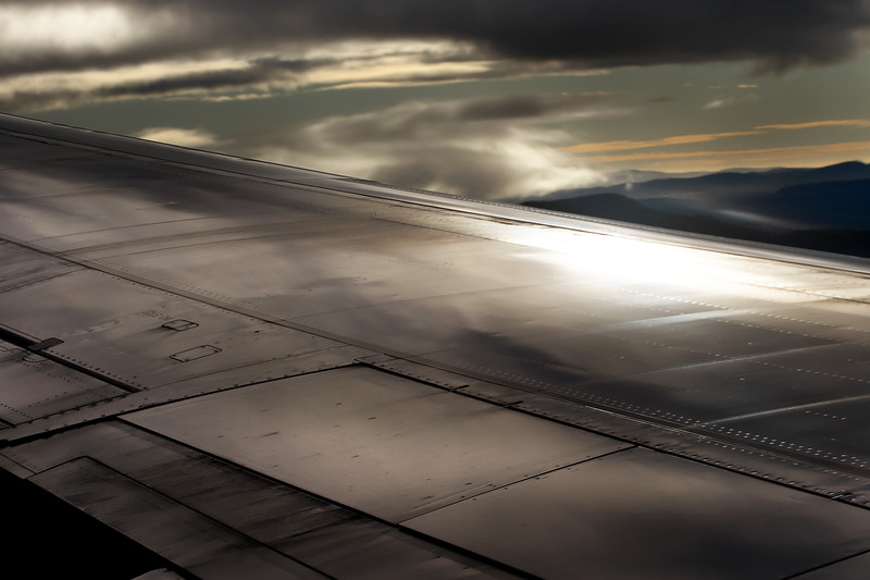 The wing of a plane with the sun reflecting off it and the Tasmanian landscape below.